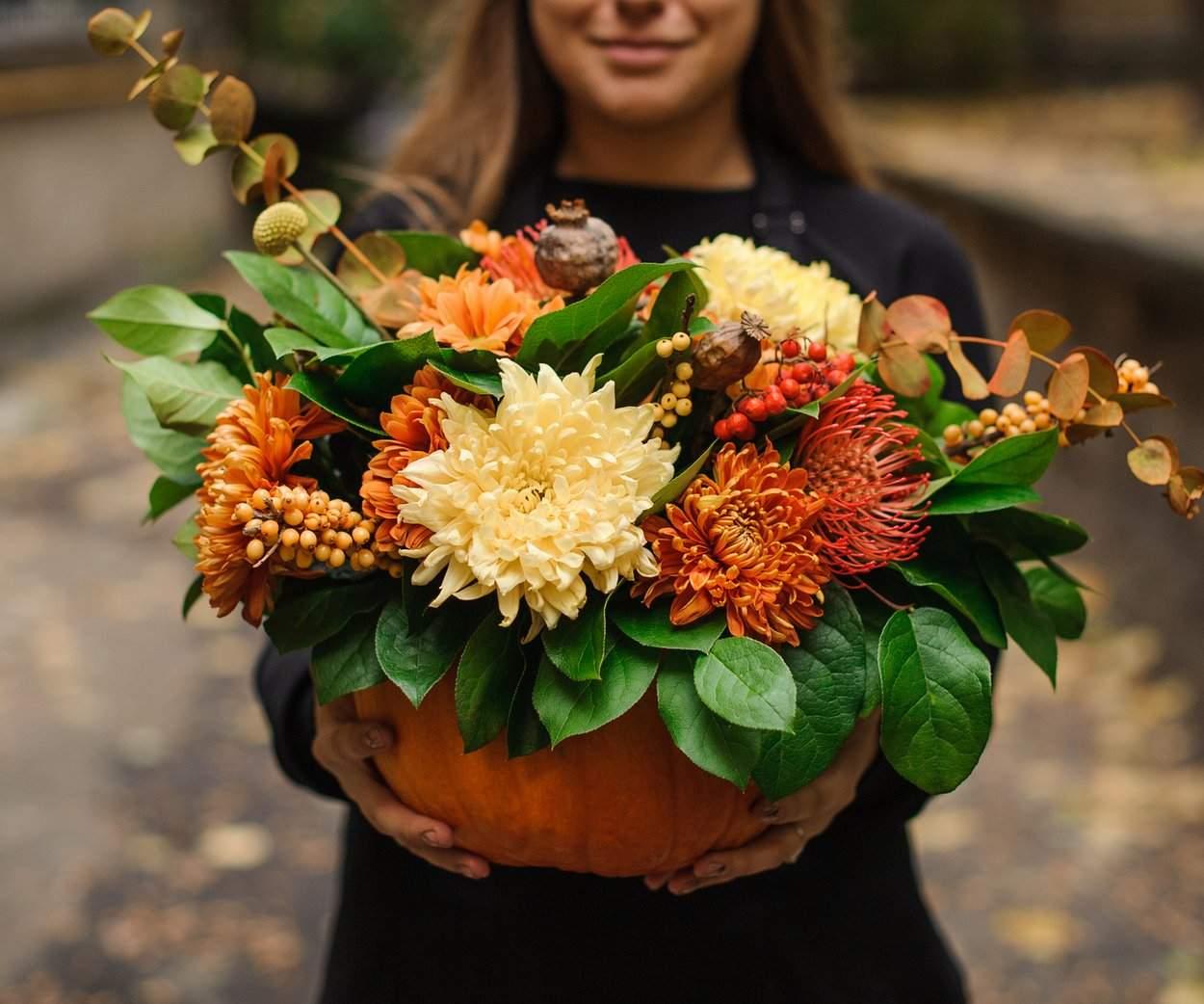 7d1e458b0bb10c19c9ddd004b6 YyAxNTkyeDEzMjcrMjY1KzQyAnJlIDEyNTAgMTA0MgNiZjdlOGIwOWQwYg== woman holding a pumpkin with autumn flowers