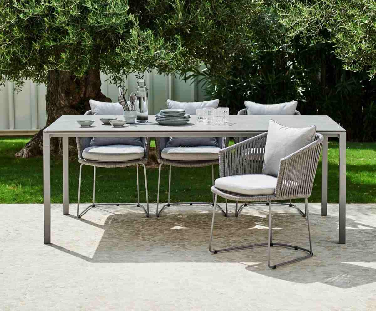 Schicker Esstisch mit passenden Stühlen im gewebtem Design für Familienessen im Garten