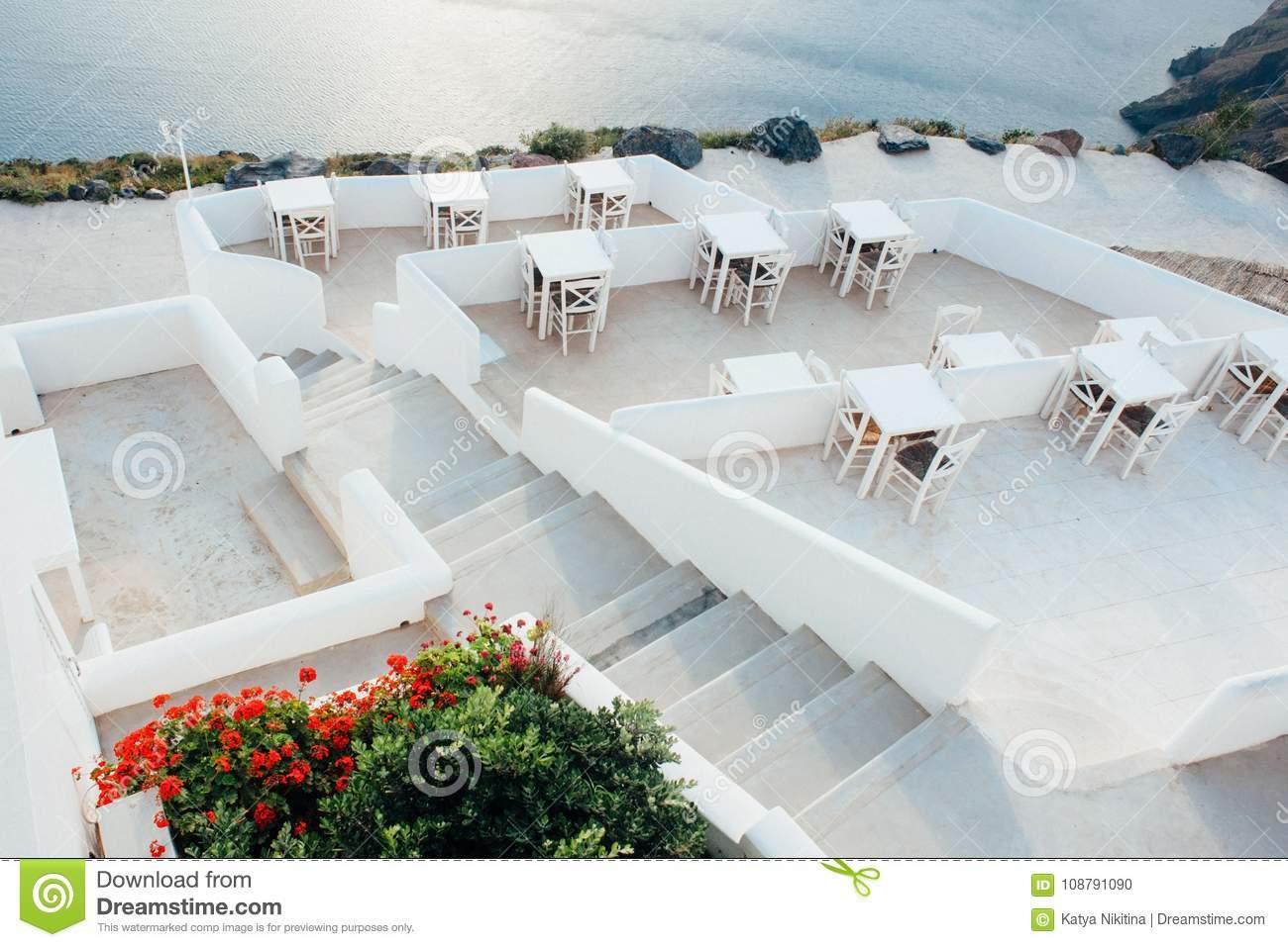 terrasse auf santorini mit treppe zum meer und weißen tabellen stühle