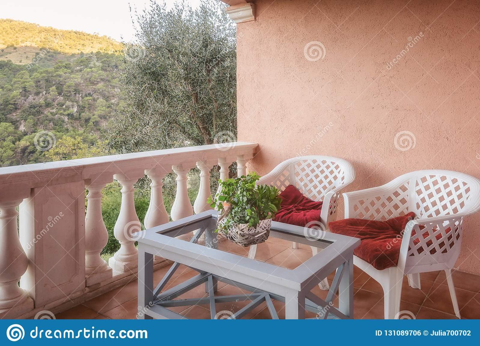 zwei stühle mit einer tabelle auf der terrasse welche berge übersieht